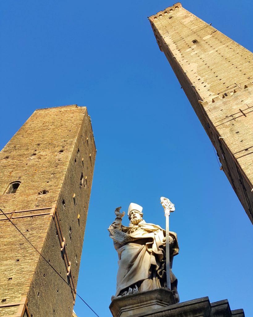 Sağda Asinelli, solda Garisenda, ortada ise Aziz Petronius'un heykeli